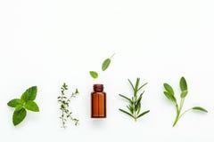 Botella de aceite esencial con el sabio herbario fresco, romero, limón foto de archivo libre de regalías