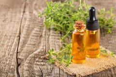 Botella de aceite esencial con tomillo de las hierbas en el fondo blanco Foto de archivo libre de regalías