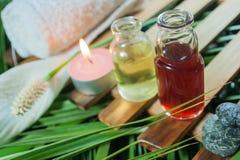 Botella de aceite esencial del aroma con la vela Fotos de archivo libres de regalías