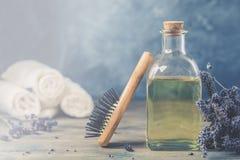 Botella de aceite de lavanda cosmético natural, tratamiento del pelo y del cuerpo, con un peine de madera del masaje fotos de archivo