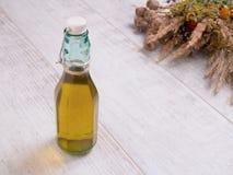 Botella de aceite y de hierbas salvajes en la tabla blanca Imagen de archivo libre de regalías