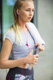 Botella de agua cansada de la abertura de la mujer después del entrenamiento Imagen de archivo libre de regalías