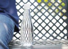 Botella de agua colocada en una silla de acero al lado de un tro que lleva del hombre fotos de archivo
