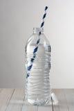 Botella de agua con la paja Foto de archivo libre de regalías