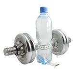Botella de agua con una cinta de medición. Imagenes de archivo