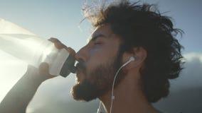 Botella de agua de consumición del hombre joven después del entrenamiento del entrenamiento almacen de video