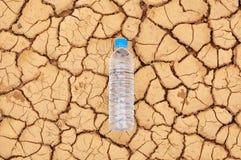 Botella de agua de consumición en fondo árido Fotografía de archivo libre de regalías