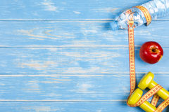 Botella de agua, de manzana, de pesas de gimnasia y de cinta de la medida en la madera azul Foto de archivo libre de regalías
