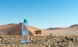 Botella de agua en el medio del desierto Foto de archivo