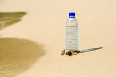 Botella de agua en la arena en la playa Fotos de archivo