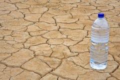 Botella de agua en la tierra seca Imágenes de archivo libres de regalías