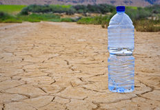 Botella de agua en la tierra seca Foto de archivo