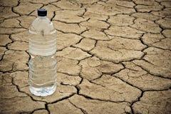 Botella de agua en la tierra seca Fotos de archivo libres de regalías