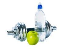 Botella de agua mineral, de pesas de gimnasia y de manzana imágenes de archivo libres de regalías