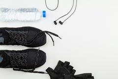 Botella de agua plástica, zapatos negros del deporte, guante y auricular en el fondo blanco fotografía de archivo
