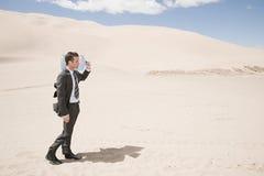 Botella de agua que lleva del hombre en desierto Foto de archivo