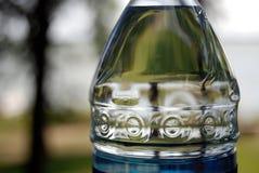 Botella de agua y lago Fotografía de archivo libre de regalías