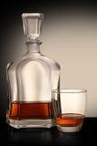 Botella de brandy con el vidrio Imagenes de archivo