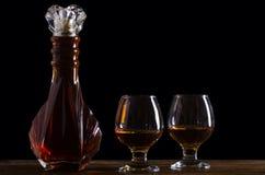 Botella de brandy y de dos vidrios en una tabla de madera Fotografía de archivo