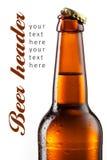 Botella de Brown de cerveza con las gotas aisladas en blanco Foto de archivo