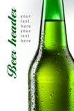Botella de cerveza con las gotas aisladas en blanco Imágenes de archivo libres de regalías