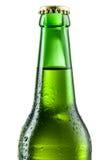 Botella de cerveza con los descensos aislados en blanco. Fotografía de archivo
