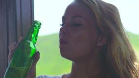 Botella de cerveza de consumición de la mujer joven en el día caliente en verano Ciérrese encima de la muchacha hermosa que goza  almacen de video