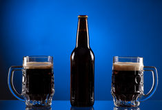 Botella de cerveza de Brown con dos tazas Imagen de archivo libre de regalías
