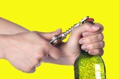 Botella de cerveza de la apertura de la mano con el abrelatas del metal Imágenes de archivo libres de regalías