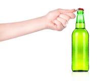Botella de cerveza de la apertura de la mano con el abrelatas del metal Imagenes de archivo