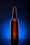 Botella de cerveza en fondo azul Imagen de archivo libre de regalías