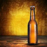 Botella de cerveza en fondo del grunge Foto de archivo libre de regalías