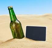 Botella de cerveza en la arena en el desierto y la pizarra Imagen de archivo