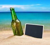 Botella de cerveza en la arena en la playa y una pizarra Fotografía de archivo