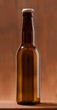 Botella de cerveza en la tabla de madera Fotos de archivo