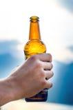 Botella de cerveza Fondo natural Los handdel hombre guardan una botella de cerveza Bebida del alcohol fotos de archivo