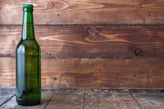 Botella de cerveza fría con espuma en la tabla de madera con el fondo de madera Imagen de archivo libre de regalías