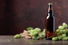 Botella de cerveza, de grano y de saltos en una tabla de madera vieja Imagenes de archivo
