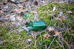 Botella de cerveza quebrada en la tierra en el bosque Imagen de archivo