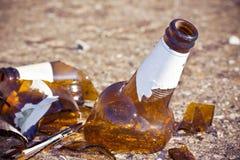 Botella de cerveza rota que descansa sobre la tierra: concepto del alcoholismo Imagenes de archivo