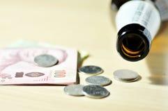 Botella de cerveza vacía con los billetes de banco y las monedas Foto de archivo