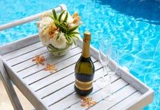 Botella de champán con los vidrios y las flores Fotos de archivo libres de regalías