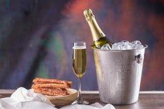 Botella de Champán en cubo con hielo y vidrios de champán encendido Foto de archivo libre de regalías