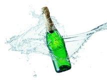 Botella de champán en el chapoteo del agua aislado en el backgr blanco Imagen de archivo