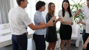 Botella de Champán en las manos del hombre de negocios al lado de los colegas que aumentan la tostada en espacio de oficina almacen de metraje de vídeo
