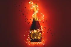 Botella de Champán envuelta en guirnalda de oro en fondo de papel rojo Día de San Valentín, cumpleaños, concepto de la celebració imágenes de archivo libres de regalías