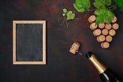 Botella de champán, manojo de la uva de corcho con las hojas y pizarra en fondo oxidado imagen de archivo