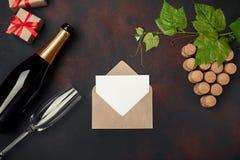 Botella de champán, manojo de la uva del corcho con las hojas caja de la copa, del sobre, de la letra y de regalo en fondo oxidad imagen de archivo libre de regalías