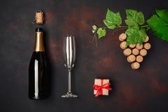 Botella de champán, manojo de la uva del corcho con las hojas, copa fotos de archivo