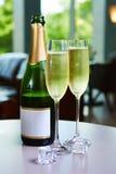 Botella de champán y de dos vidrios en la tabla Fotografía de archivo